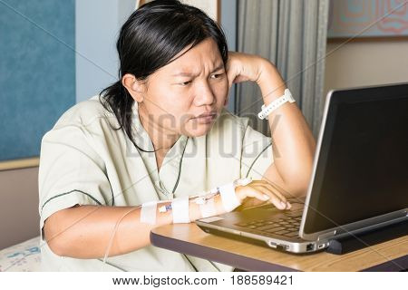 asia woman in hospital room lying in bed sick and injured using internet in computer laptop feeling concern and serious about her job