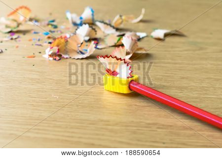The Red Color Pencils With Sharpener And Shavings On The Wood Table.