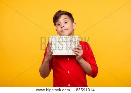 Small expressive kid holding giftbox and looking at camera on yellow background.