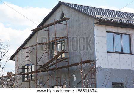 Painting Plastering Stucco and insulate Exterior House Wall. Facade Thermal Insulation and Painting Repair Works During Exterior Renovations. Wall Insulation and Repair.