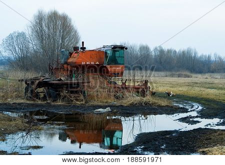Chuvashia Russia April 16 2012: Early spring in the countryside. The abandoned harvester is located near an impassable dirty rural road. Chickens walk nearby.