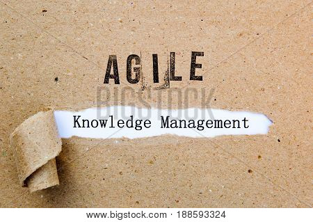 Agile Knowledge Management - printed text underneath torn brown paper with Agile printed in ink
