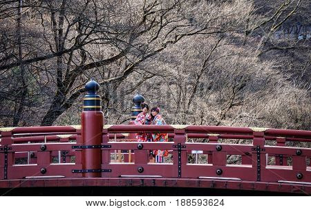 Nikko Japan - Apr 1, 2016. Women in traditional dress (kimono) visiting the red sacred Shinkyo bridge in Nikko Japan.
