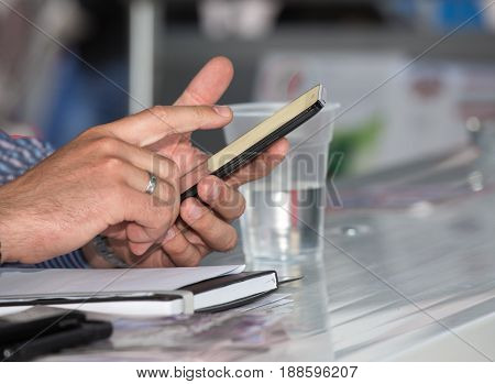 Close up of businesman's hands holding smartphone and touching screen at desk
