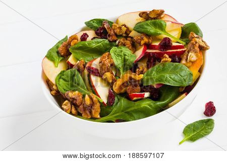 Fruit salad with fresh apples dried cranberries spinach and walnuts in a white bowl on the wooden table.