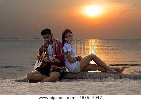 Cute hispanic couple playing guitar serenading on beach in love and embrace sunset in the beach