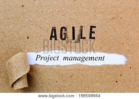 Agile Project Management - printed text underneath torn brown paper with Agile printed in ink