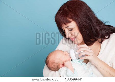 mom is feeding the baby milk from a bottle of love family