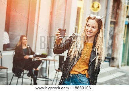 Beautiful young stylish woman wear in fashion clothes and staying in front of cafe and holding black cup of coffee, enjoying, smiling and look at cam. Lifestyle, fashion, street style concept.