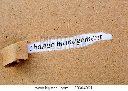 Change Management - printed text underneath torn brown paper