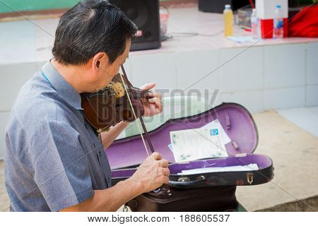 CHIANG RAI THAILAND - FEBRUARY 19 : Unidentified asian musician playing the violin outdoors on February 19 2016 in Chiang rai Thailand.