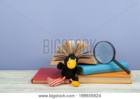 Open book, hardback colorful books on wooden table. Magnifier, toy crow. Back to school. Copy space for text