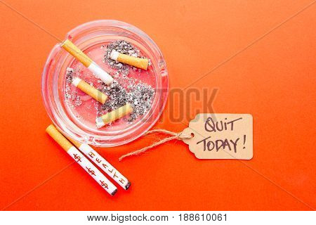 Stop Smoking - Quit Now - with cigarettes and ashtray on printed background