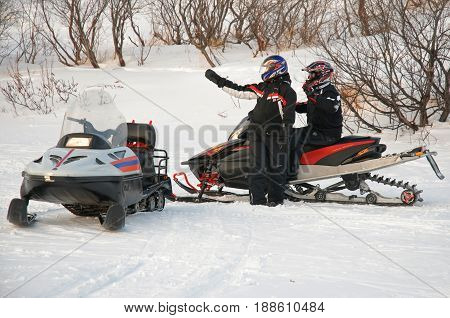 Murmansk, Russia - February 15, 2010: The driver of a snowmobile indicates the way to another friend