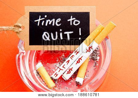 Quit Smoking - Time to Quit - cigarettes, ashtray and blackboard on red background