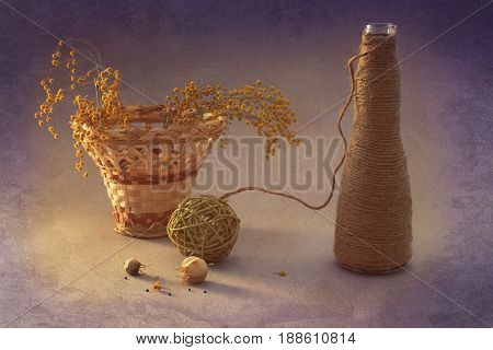 Still life with Mimosa and wicker basket. Bottle with linen thread.