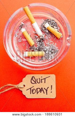 Stop Smoking - Quit Today - with cigarettes, ashtray and tag on red background