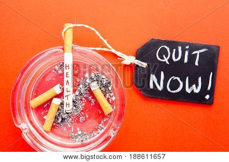 Quit Now - Stop Smoking - Health - with cigarettes, ashtray and blackboard on red background