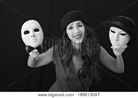 Girl mime holds in her hands two theatrical masks