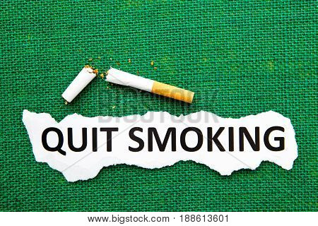 Quit Smoking - with broken cigarette and printed text on green burlap background