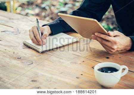 Business Man Hand Writing Note Pad And Holding Tablet In Coffee Shop With Vintage Filter.