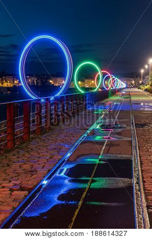 The luminous rings on the Nantes island by night with the light reflection on the puddles