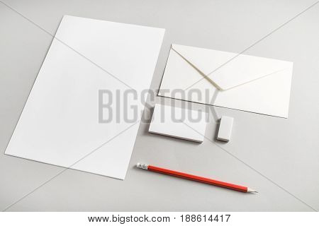 Photo of blank stationery set on paper background. Corporate identity template for placing your design. Blank letterhead business cards envelope eraser and pencil. Top view.