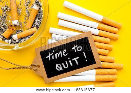No Smoking - Time to Quit - with cigarettes, ashtray and handwritten blackboard on yellow background