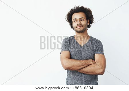 Portrait of stong and handsome african man looking at camera posing with crossed arms over white background. Confident entrepreneur or student. Copy space.