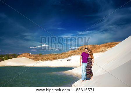 Beach couple on romantic travel honeymoon vacation summer holidays romance. Young happy lovers, caucasian woman and man embracing outdoors