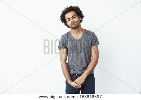 Bored dull tired african man looking at camera over white background. Copy space.