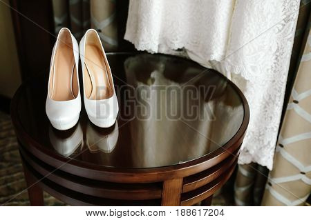 Luxury stylish white wedding shoes on wooden table with a dress in background. Morning preparetion.