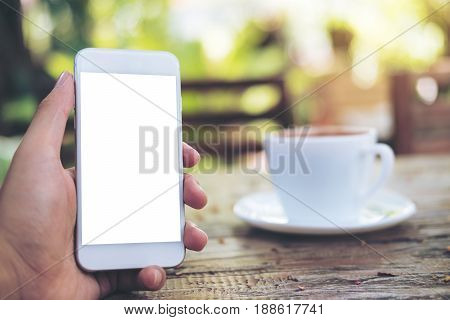 Mockup image of hands holding white mobile phone with blank screen and hot coffee cup on wooden table with blur green nature background
