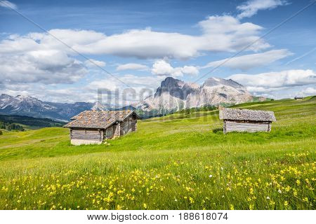 Beautiful view of idyllic alpine mountain scenery with traditional old mountain chalets and fresh green meadows on a sunny day with blue sky and clouds in springtime Alpe di Siusi South Tyrol Italy