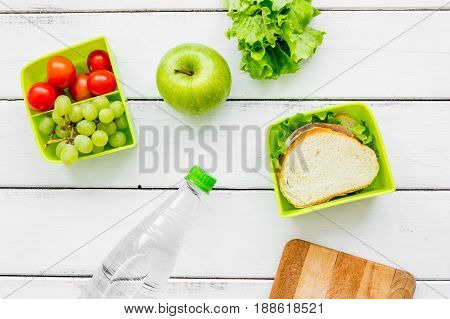 homemade lunch with apple, grape and sandwich in green lunchbox on white wooden table background top view