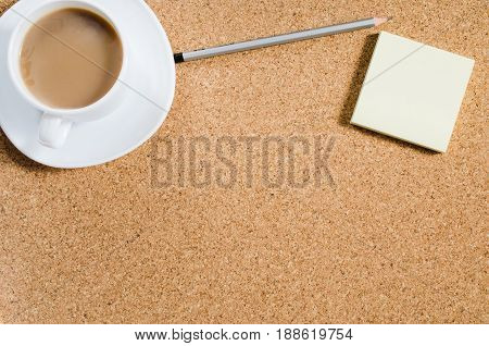 Top view image of blank notes next to cup of coffee on cork board. Ready for adding text or mockup. Flat lay.