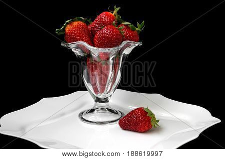 strawberries in a vase on a black background.