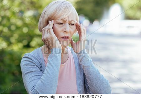 Awful pain in temples. Retired frustrated distracted woman touching her temple and expressing frustration while suffering from headache outdoors