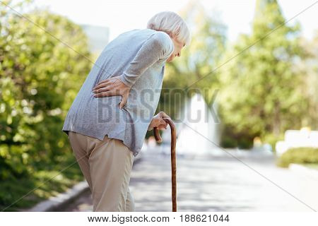 Heavy steps . Involved unhealthy aged woman touching her back and leaning on the stick while having backache outdoors