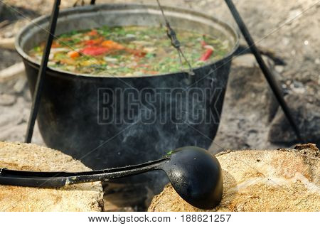 The soup is cooked in a cauldron at the stake. Smoke comes from the fire. In the foreground lies a black chopstick on the log.