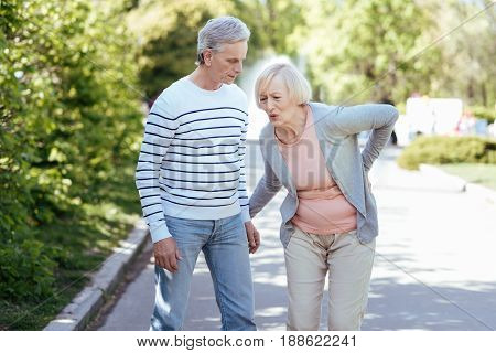 Ready to help you. Senior helpful attentive man caring about his aging wife and helping her while walking outdoors
