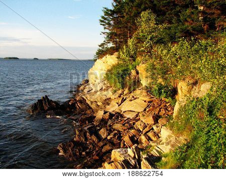 Casco bay Maine's rocky shoreline with the sun shining on the rocks.