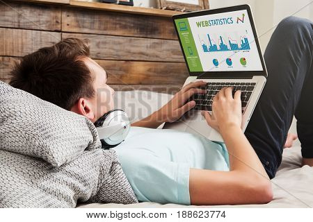 Man consulting web statistics in a laptop computer at home.