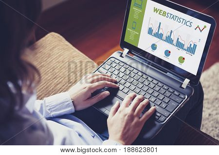 Web statistics consulting. Woman using a laptop computer to analyze web statistics.