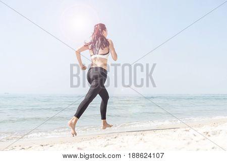 Young beautiful sportive girl runing over seaside.