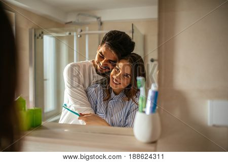 Portrait of a couple bonding over daily morning routine in the bathroom.