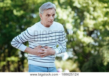 Unpredictable symptom. Retired frustrated unhappy man touching his belly and expressing frustration while suffering from stomachache outdoors