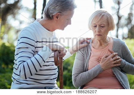 Everyday problems of aged generation. Frustrated weak old woman touching her chest and having heart attack while her aged husband worrying about her and sitting on the bench outdoors
