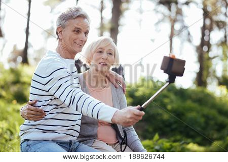 Like young again. Happy joyful old couple hugging each other and using selfie stick while enjoying weather in the park and taking pictures