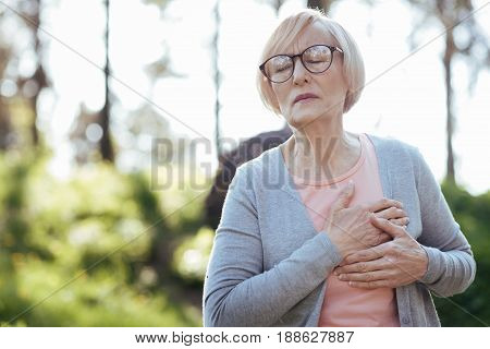 Influence of negative emotions . Upset ill weak woman touching her chest and feeling pain while sitting outdoors